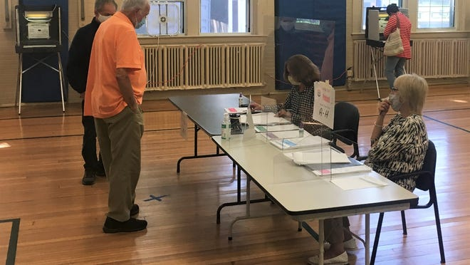 Voters prepare to cast their ballots at Precinct 1 in Plymouth during Tuesday's state primary.