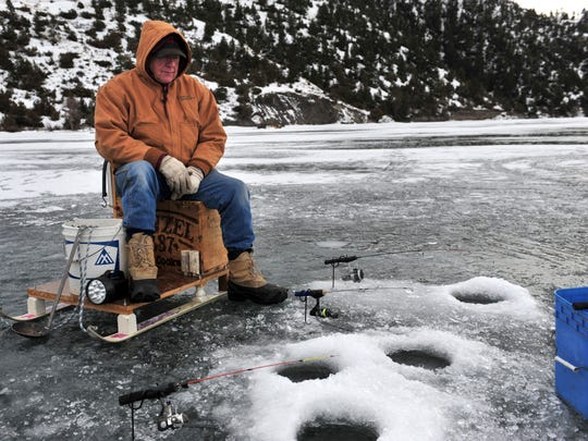 Bill Claassen keeps an eye on his poles while ice fishing at Holter Lake, Wednesday.
