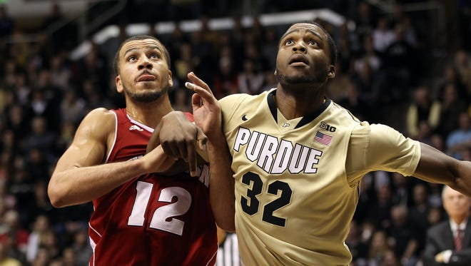 Wisconsin Badgers guard Traevon Jackson (12) and Purdue Boilermakers forward Errick Peck (32) battle for position during the second half at Mackey Arena.