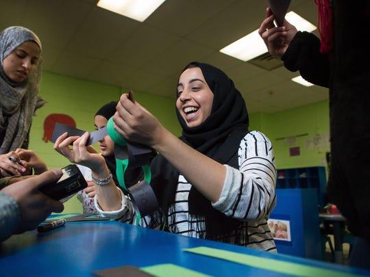 Newark residents Rania Almoraisi (from left), 16, Reem
