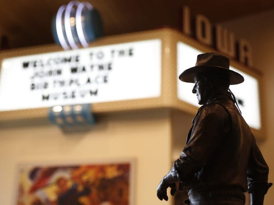 A John Wayne statue stands among the gift shop items in front of the theater in 2015 inside the John Wayne Birthplace Museum in Winterset, Ia.