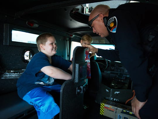 LCPD Officer Juan Gomez, right, inside of a SWAT vehicle known as a Barecat, explains the use of a SWAT officer's shield to Gabriel Hoover, 8, Wednesday, August 3, 2016, during Gabriel's tour of the LCPD headquarters.