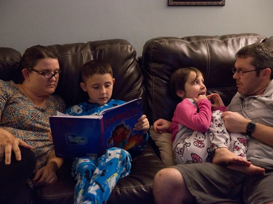Hillary Melchiors and her husband, Andy Melchiors, read bedtime stories with daughters, Annika, 8, and Mayzie, 6.