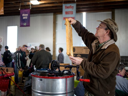 Dave Agar, of Kimball Township, inspects honeycomb before putting it into a hand-operated centrifuge extractor at the Pine River Beekeeping Club booth during the Earth Fair Friday, April 28, 2017 at Goodells County Park.