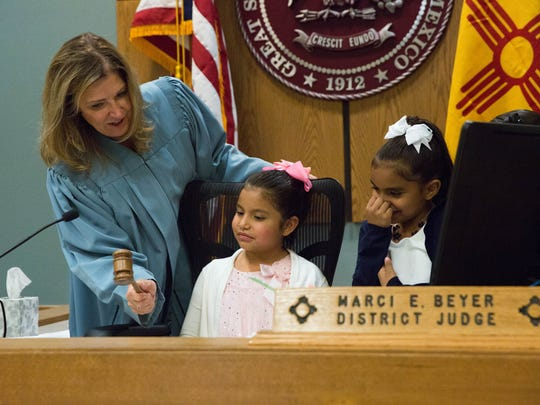 Judge Marci E. Beyer, left, of the Third Judicial District Court, shows twin sisters Natalie Mendez, center, and Joveigh Mendez, right, how to use the gavel, after they were officially adopted by Maria Mendez, Tuesday November 14, 2017.