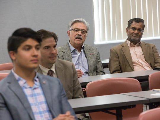 Rolando Flores,center, dean of the College of Agriculture, Consumer and Environmental Sciences at New Mexico State University, speaks about trying to find a chancellor candidate that understands the university's standing as a land grant institution, Tuesday, April 3, 2018, during a news conference.