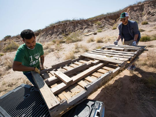 Angel Peña, left with Conservation Lands Foundation and Patrick Nolan, right, executive director of Friends of the Organ Mountains-Desert Peaks National Monument, lift wood pallets into Peña's truck during a cleanup event put on by the Friends group, and other organizations on Monday May 21, 2018, on the fourth anniversary of the designation of the monument.