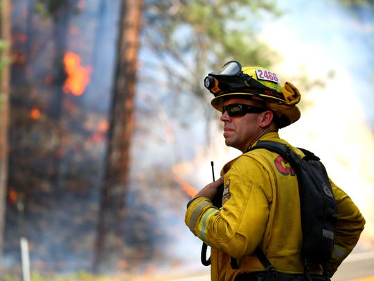 Todd Abercrombie, of Cal Fire watches the fire behavior as firefighters monitor fire movement as it crosses Highway 299 just west of Buckhorn Summit near the Trinity County line in Redding, California, on July 30, 2018.