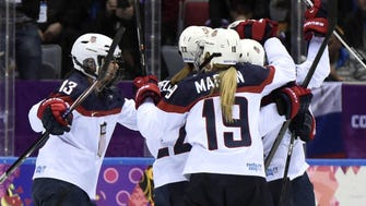 Team USA players celebrate after a goal by forward Meghan Duggan during the 2014 Sochi Olympics.