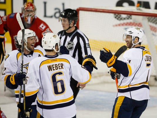 Nashville Predators' Matt Cullen, right, celebrates his goal with teammates Mike Fisher, left, and Shea Weber during the third period of an NHL hockey game against the Calgary Flames in Calgary, Alberta, Friday, March 21, 2014. The Predators won 6-5. (AP Photo/The Canadian Press, Jeff McIntosh)