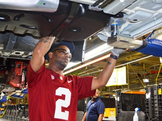An assembly line worker builds cars while wearing an Alabama jersey Monday at the Hyundai plant in Montgomery.