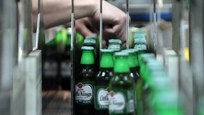 Bottles of Little Kings Cream Ale are adjusted as they move into a packaging machine.