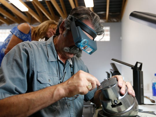 Jim Downing engraves letters on a piece of metal for