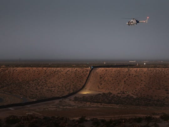 A Customs and Border Patrol Air and Marine Operations helicopter flies past the border wall in Sunland Park, N.M., Sunday.