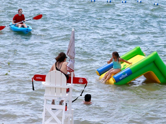 Lifeguard supervisor Lauri Roberts-Nutt keeps an eye on the swimmers during opening day for the designated swimming area on Friday May 27, 2016, at Farmington Lake.