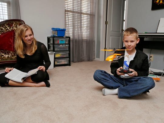 Abigail Putman, 14, watches as her brother Jonathan, 11, flies an RC helicopter Monday, November 24, 2014, in their Lafayette home. An upstairs room serves as the homeschooling classroom for all four Putman children.