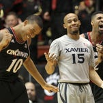 From left: UC guard Troy Caupain, Xavier guard Myles Davis and UC forward Octavius Ellis react after a turnover during the Crosstown Shootout in February.