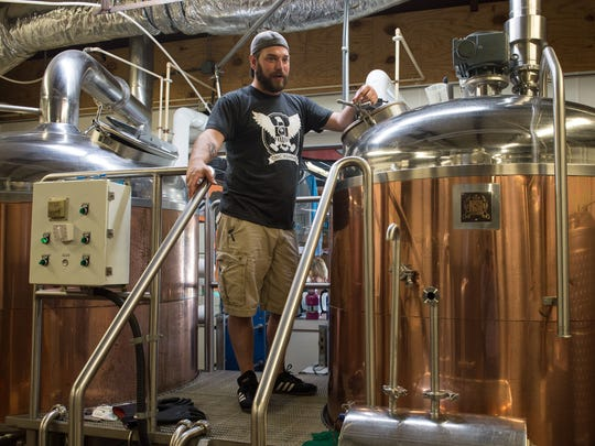 John Panasiewicz, Brewmaster for 3rd Wave Brewing, stands next to a mash tun while explaining the brewing process.