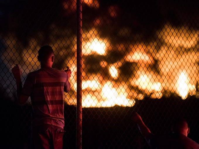 Pedestrian watch as a four-alarm junkyard fire burns