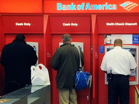 Customers use ATM machines at a Bank of America branch