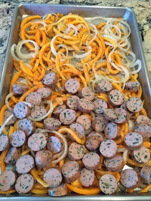 """Butternut squash """"noodles,"""" sliced onion and chicken sausage are roasted together for this one-dish meal."""
