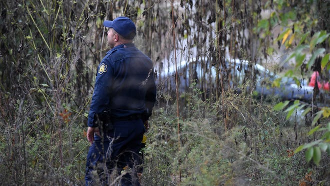 Arkansas State Trooper Jackie Stinnett searches a wooded area Wednesday night in County Life Mobile Home Park in Midway for 25-year-old Midway man John Robinson, who ran from officers. Robinson is alleged to have assaulted an 8-year-old child.