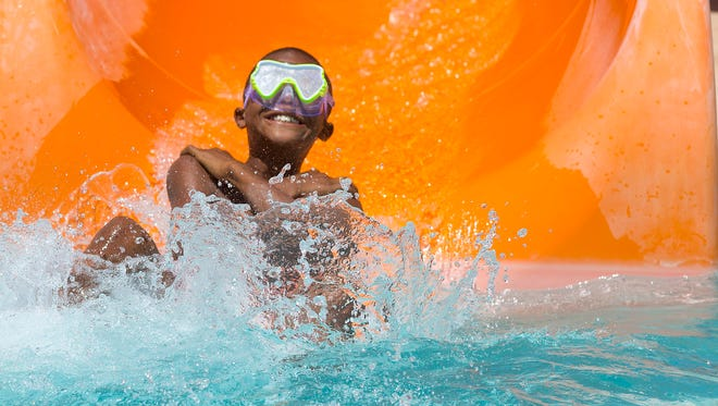 Kyree Harris, 9, of Phoenix, slides into the water at Cortez Pool in Phoenix on May 28, 2016.