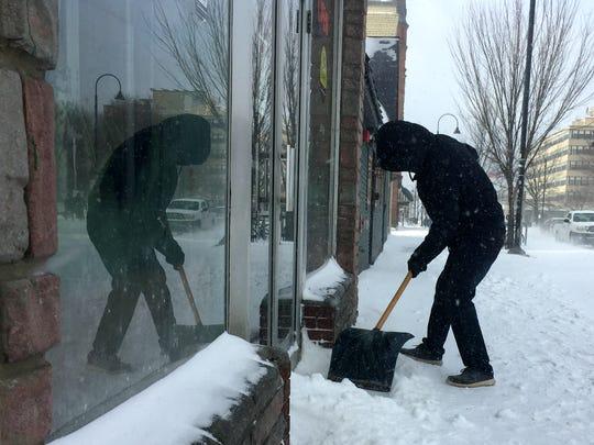 Shouxian Li, owner of Fu Da restaurant in Burlington, shovels the Pearl Street entrance on Saturday, Jan. 13, 2018.