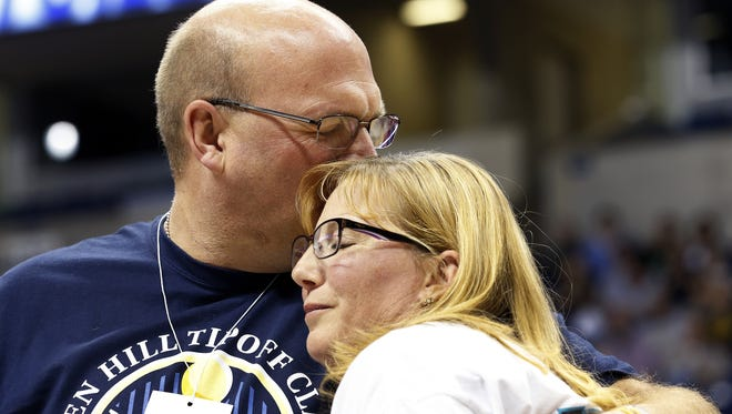 Brent and Lisa Hill embrace, while watching a video featuring their daughter, Lauren, during halftime of the Mount Saint Joseph University and Hiram College game at the Lauren Hill Tipoff Classic at the Cintas Center Saturday, November 14, 2015.