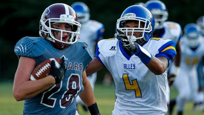 Holy Cross running back Mario Convenuto (28) is chased by Valley defensive back Darrell Williams (4). Aug. 25, 2017