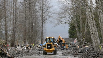 OSO, WA - MARCH 25:  Crews work on Washington State Route 530 to clear debris from a mudslide on March 25, 2014 in Oso, Washington. A massive mudslide on March 22 has killed at least fourteen and left scores missing.  (Photo by Ted S. Warren-Pool/Getty Images)