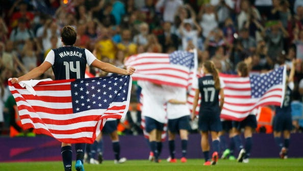 Abby Wambach celebrates with the American flag after defeating Japan by a score of 2-1 to win the Women's Football gold medal match on Day 13 of the London 2012 Olympic Games at Wembley Stadium.