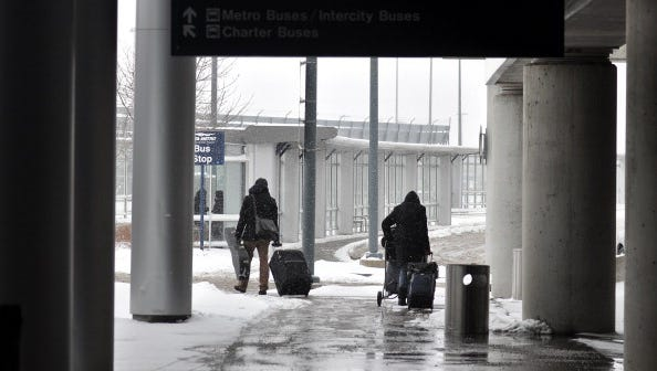 Travelers leave the Buffalo International airport as lake effect snow bands again set up on December 14, 2010 .