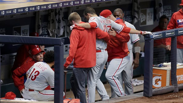 The Phillies' Charlie Morton is helped off the field after getting injured while running to first base in the second inning against the Brewers at Miller Park on Saturday in Milwaukee.