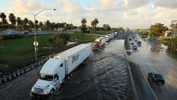Trucks move through flood waters on southbound Highway 710 in Long Beach last month during a wet period that caused millions in dollars in damage to state highways. California Governor Jerry Brown is in Riverside Tuesday to promote a proposed gas tax increase that would help pay for road repairs across California.