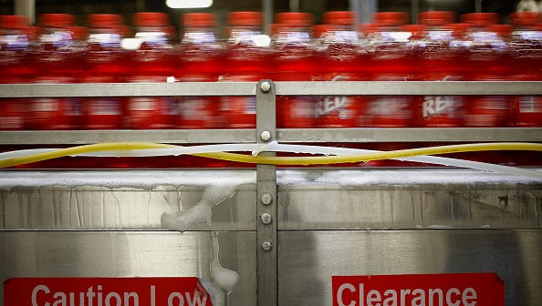 Bottles of Big Red soda move down a conveyor belt after being bottled at the Dr. Pepper Snapple Group Inc. bottling plant in Louisville, Kentucky, U.S., on Tuesday, April 21, 2015. Dr. Pepper Snapple Group Inc., producers of 7up and A&W Root Beer, is scheduled to release earnings figures on April 23. Photographer: Luke Sharrett/Bloomberg via Getty Images