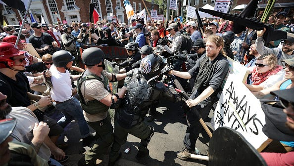 "White nationalists, neo-Nazis and members of the ""alt-right"" clash with counter-protesters as they enter Lee Park during the ""Unite the Right"" rally Aug. 12, 2017, in Charlottesville, Virginia. After clashes with anti-fascist protesters and police the rally was declared an unlawful gathering and people were forced out of Lee Park, where a statue of Confederate General Robert E. Lee is slated to be removed."