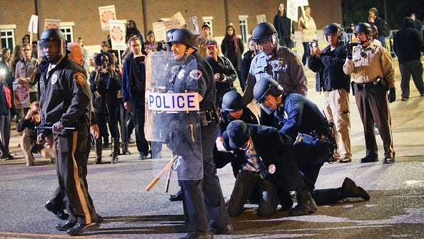 FERGUSON, MO - OCTOBER 22:  Police arrest a demonstrator outside the police station as protests continue in the wake of 18-year-old Michael Brown's death on October 22, 2014 in Ferguson, Missouri. Several days of civil unrest followed the August 9 shooting death of Brown by Ferguson police officer Darren Wilson. Today's protest was scheduled to coincide with a day of action planned to take place nationwide to draw attention to police brutality.  (Photo by Scott Olson/Getty Images)