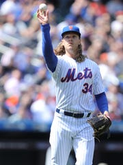 Noah Syndergaard tosses the ball to first base after