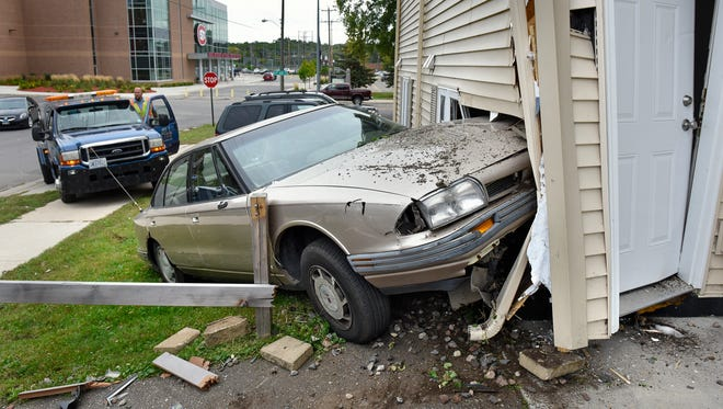 A tow truck driver gets ready to remove a car from the side of a building Wednesday, Sept. 21, at 1302 Fifth Ave. S. in St. Coud. City building officials were on scene to determine if the apartment building will still be safe to live in.  The building is home to several St. Cloud State hockey players.