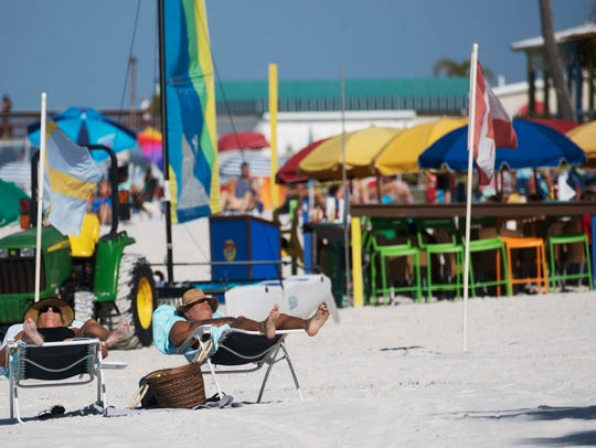Beachgoers get some sun in front of the Pierview Hotel and Salty Crab restaurant on Fort Myers Beach.