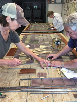 Mike Winters and  Belt workshop participants: Amy Olson (front)  and Marilyn Enderson restoring a prism glass transom window.