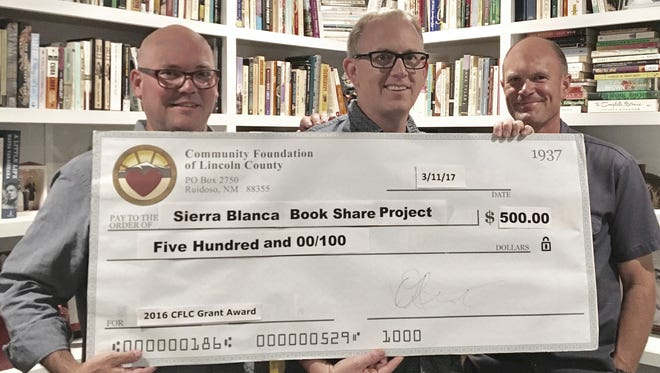 Holding the big check from left are Leroy Smith with the Community Foundation of Lincoln County, and Tim Lewis and Luther Light, with the Sierra Blanca Book Share Project.