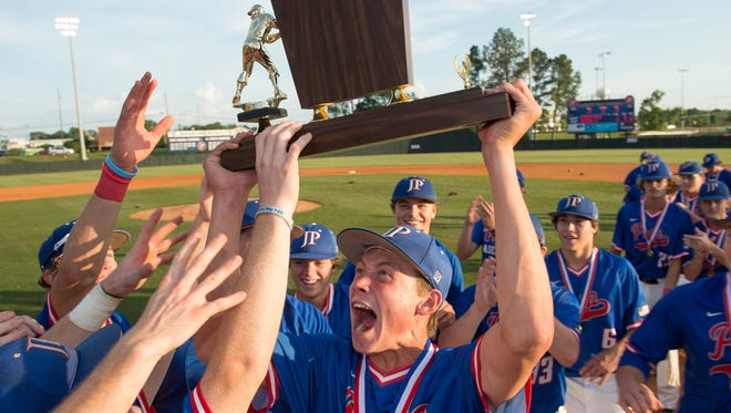 Jackson Prep players celebrate with the trophy following the Patriots' 4-1 win over Jackson Academy Thursday in Flowood.