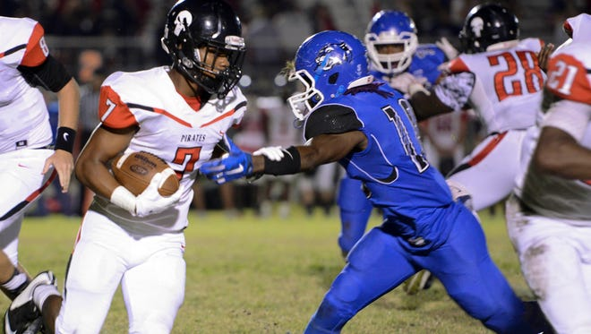 Palm Bay's Ken McKay runs around the tackle of Heritage player Benjamin Williams during Friday's game.