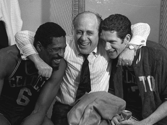 Boston Celtics general manager Red Auerbach hugs the stars of the Celtics' NBA championship win over the Los Angeles Lakers, Bill Russell, left, and John Havlicek, in Los Angeles on May 3, 1968.