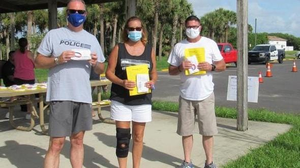 From left, Flagler Police Chief Matt Doughney, Mayor LInda Provencher and Fire Chief Bobby Pace at the mask giveaway Saturday.