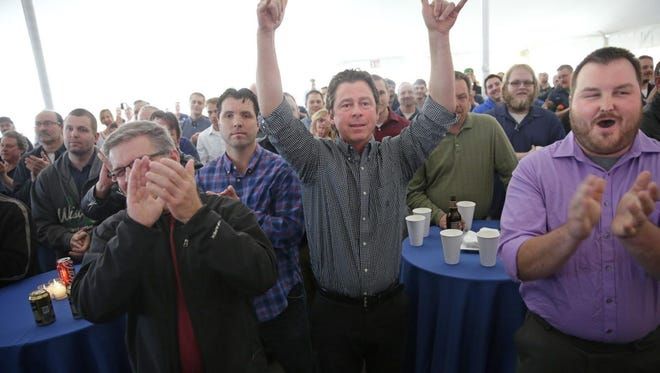 Greg Winn, center, a Paper Machinery Corp. tool designer for 36 years reacts to the announcement, with Chad Leonard, far right, a tool designer for 3 years, that they would become owners of the Milwaukee company Paper Machinery.
