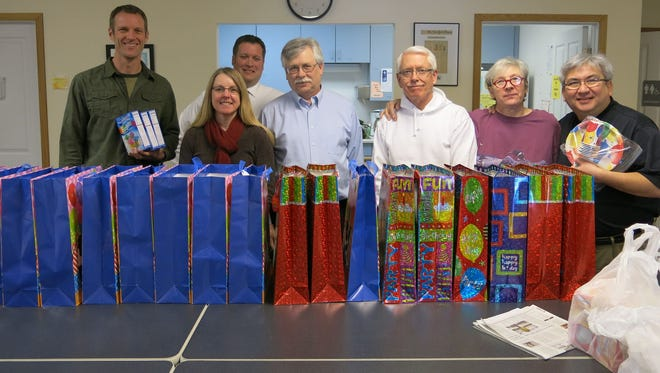 """Members of the Rotary Club of Iowa City Downtown pose with """"birthday bags"""" filled at The Crisis Center in February. Sandy Pickup (second from far-right) is retiring at the end of this month."""