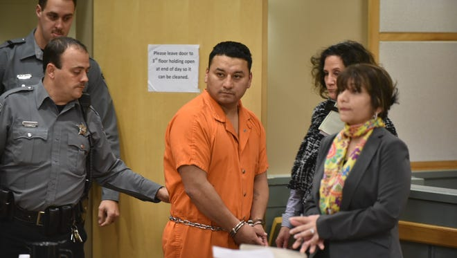 Ricardo C. Santiago is led into a courtroom at the Cumberland County Courthouse Thursday for his arraignment.